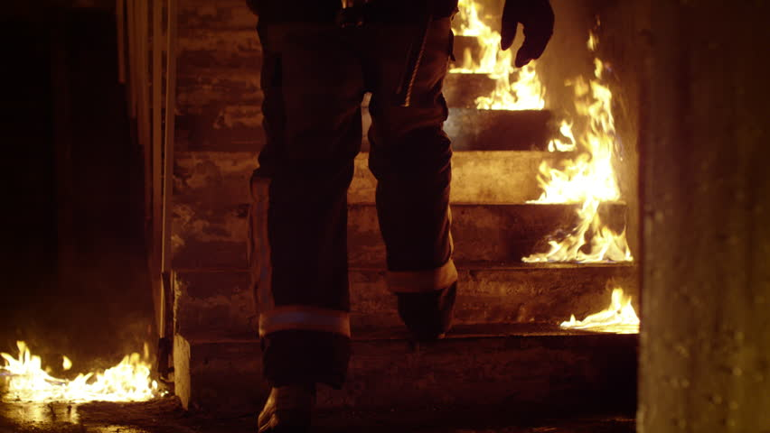 Close-up of a Firefighter's Legs Running Up the Burning Stairs. Building is on Fire Open Flames are Seen Everywhere. Slow Motion.  Shot on RED EPIC 4K (UHD).