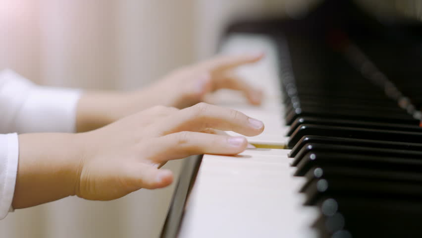 Child playing piano. Side view of a child playing piano. Close up on piano keys, child hands and fingers. | Shutterstock HD Video #22874221