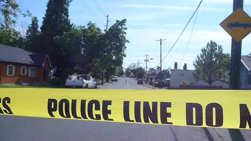 Police caution line reads Do Not Cross in residential neighborhood street