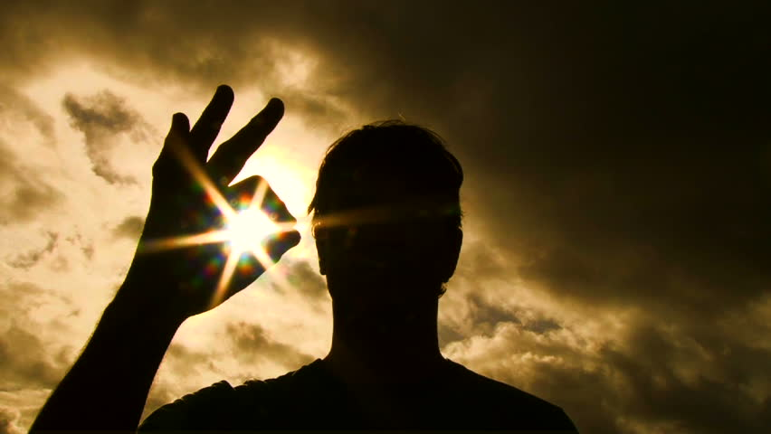 Person silhouetted raises hand into frame to give an a-okay sign with sun