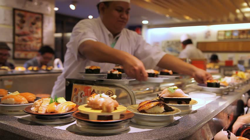 TOKYO, JAPAN - OCTOBER 10, 2014: A chef prepares sushi as other dishes go around on the conveyor belt in a busy open kitchen Japanese restaurant on October 10, 2014 in Tokyo, Japan