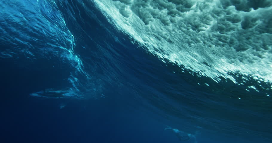 Under water view of blue ocean wave from behind. Barreling wave with sunlight and bubbles | Shutterstock HD Video #23059621