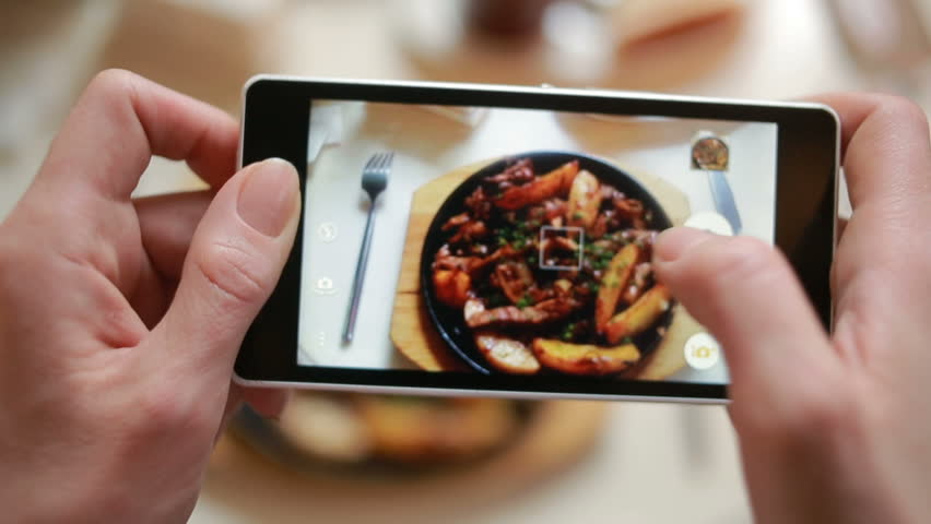 Trendy man in a restaurant make photo of food with mobile phone camera | Shutterstock Video #23145481