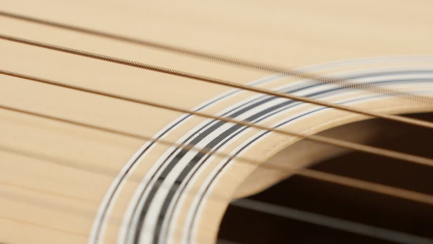 Plucked guitar E string wooden acoustic shallow DOF 4K 2160p 30fps UltraHD panning footage - Detailed instrument body slow pan 3840X2160 UHD video