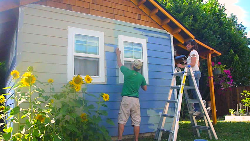 Man and woman couple paint new construction in the summer, time lapse series.