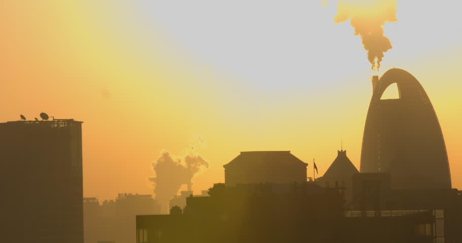 Beijing, China - December 2014: Smoke pollution from factories in city skyline at sunset. Beijing, China.