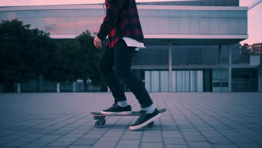Fashionable rider in hipster red plaid shirt and black jeans just skates on his longboard at twilight time with beautiful paster lightning, camera follows him | Shutterstock Video #23582533
