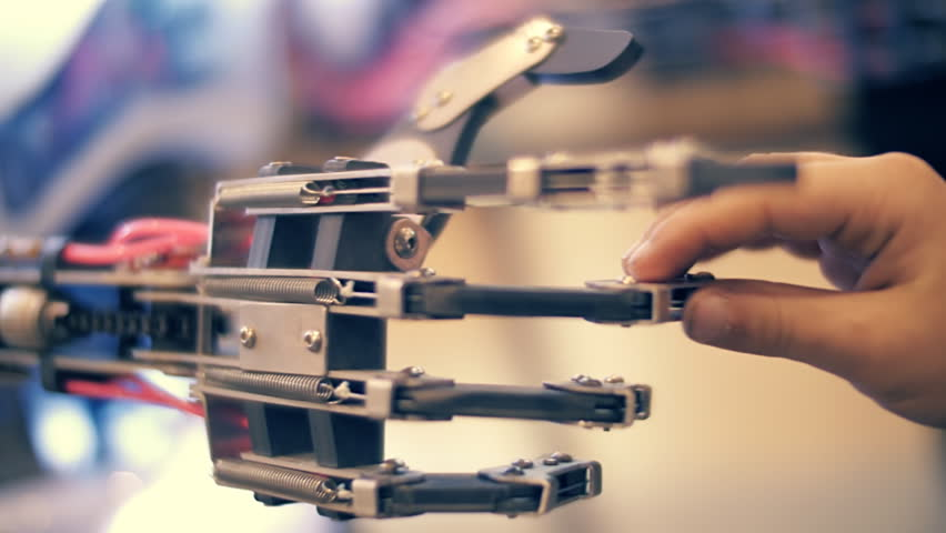 A robotic arm moves the metal fingers and child fingers gently touch them. The symbolic meeting, contact