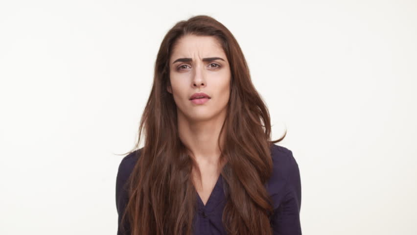 Confused beautiful Caucasian female with long brown hair standing over white background saying why shrugging her shoulders in slowmotion