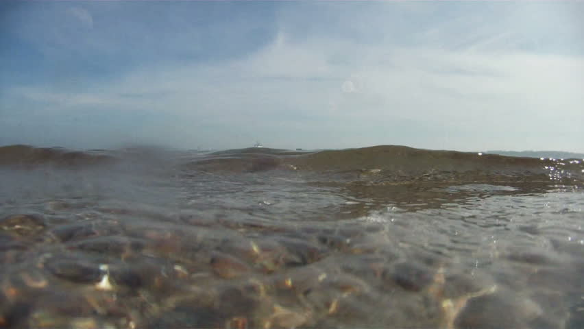Cargo ship and boats on horizon with rolling waves, underwater camera