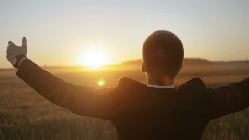 Slow motion of man in suit raising his hands up against the sun. Young man feeling a sense of accomplishment.