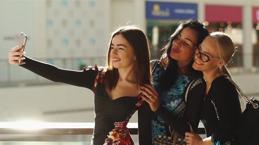 Charmed women taking selfie after shopping. Girls...