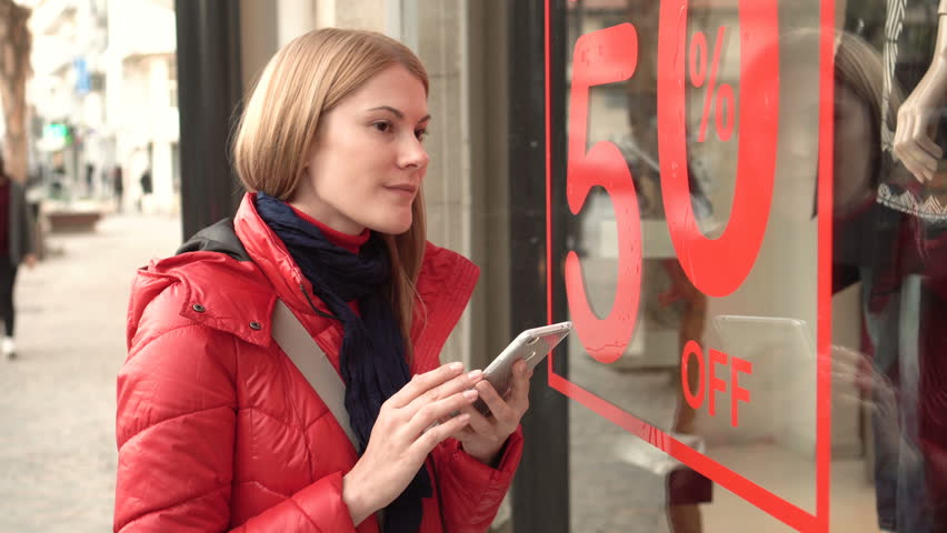 Beautiful attractive young woman near window shop. Sales signs. Reading QR-codes by smartphone.