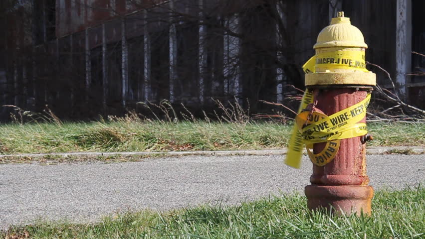 Urban blight in Detroit, Michigan. An old fire hydrant wrapped in caution tape