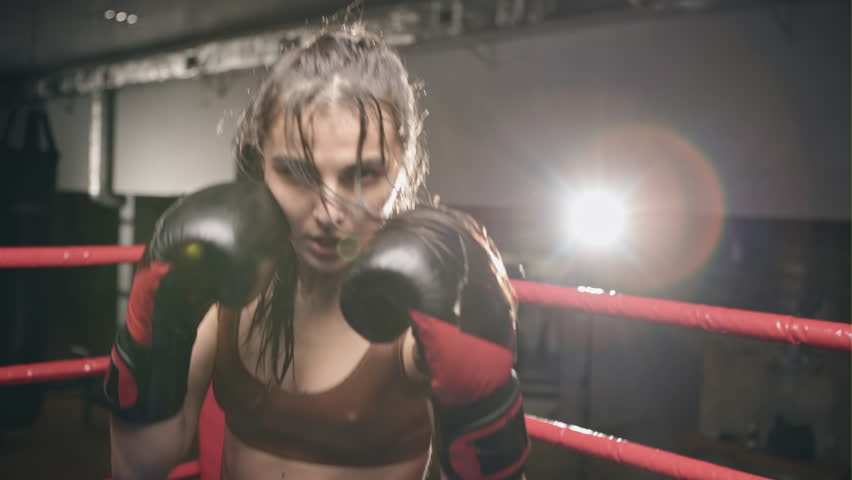 Fighter woman fist close up - boxer strikes into the side of the camcorder. Spectator video boxing