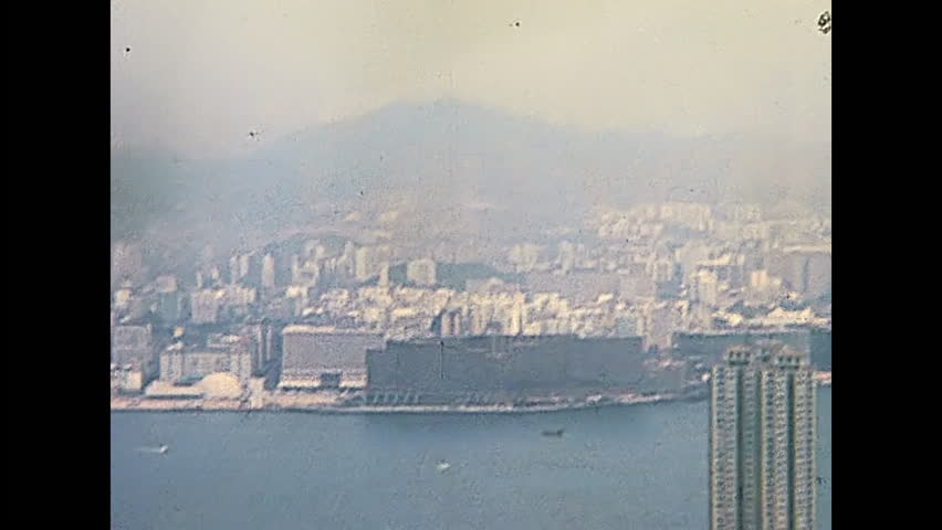 Panorama of Victoria Harbour skyline from the Peak Tower overlook, with art museum, InterContinental Hong Kong hotel and Avenue of Stars. Historic restored footage on 1980 with few buildings.
