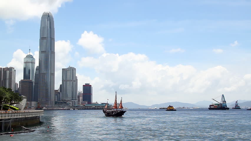 Chinese Junkboat sailing across Victoria Harbour and city skyline, Hong Kong.