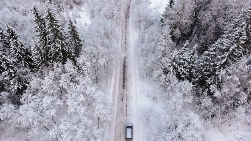 Silver car driving on winter country road in snowy forest, aerial view from drone