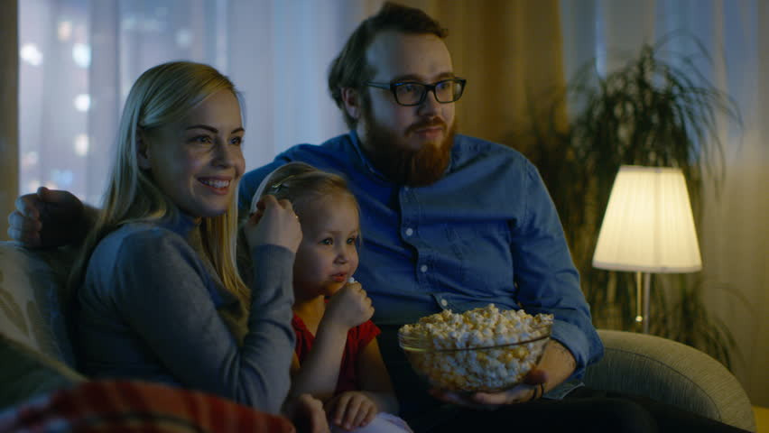 Father, Mother and Little Girl Watching TV. They Sit on a Sofa in Their Cozy Living Room and Eat Popcorn. It's Evening. Shot on RED EPIC-W 8K Helium Cinema Camera.