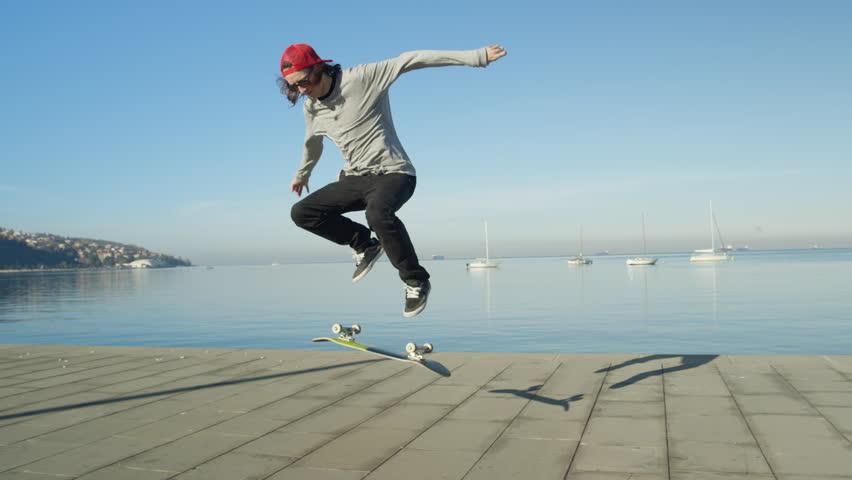 CLOSE UP SLOW MOTION DOF skateboarder skateboarding, jumping ollie flip trick on promenade along the coast on sunny day. Skateboarder jumping kickflip trick with skateboard on the beach | Shutterstock Video #24656714