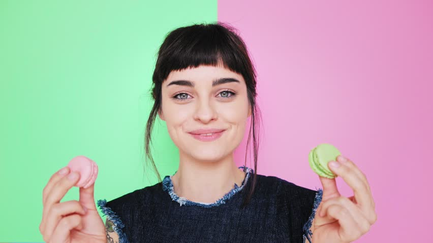 Attractive smiling young brunette isolated on splitted pistachio and rose red background holds two tasty cookies in her hands and makes her choice, then bite left macaron in pastel pink color | Shutterstock HD Video #24691346