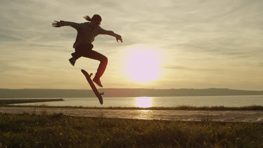 SLOW MOTION, CLOSE UP: Silhouetted skateboarder skateboarding and jumping hardflip trick on boulevard along the ocean at golden light sunset. Skateboarder riding skateboard at sunrise at seaside | Shutterstock Video #24723827