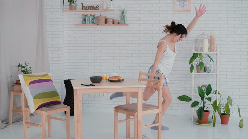 Funny young woman dancing in kitchen wearing pajamas in the morning. Brunette girl in cheerful mood listens music.