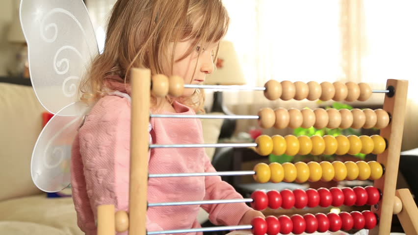 Two years old child girl playing with abacus in nursery
