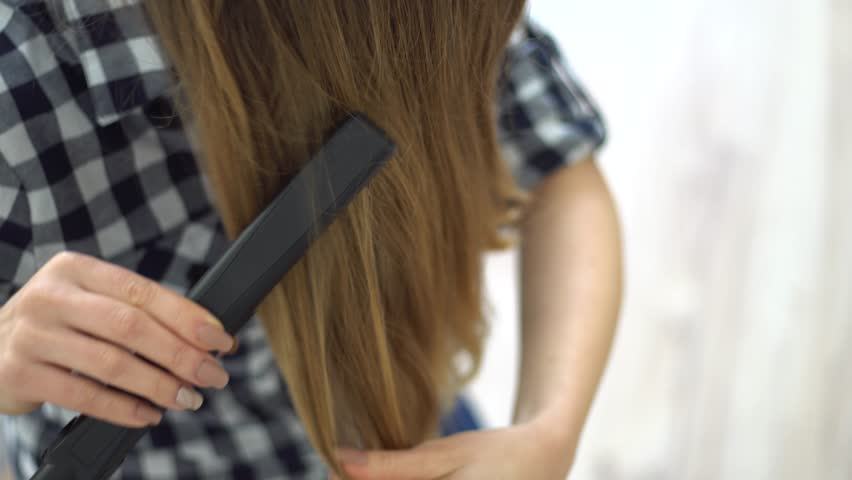 Woman doing hairstyle with hair straightener   Shutterstock HD Video #24908396