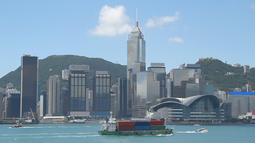 Small container ship crossing the victoria habour and city skyline, Hong Kong.