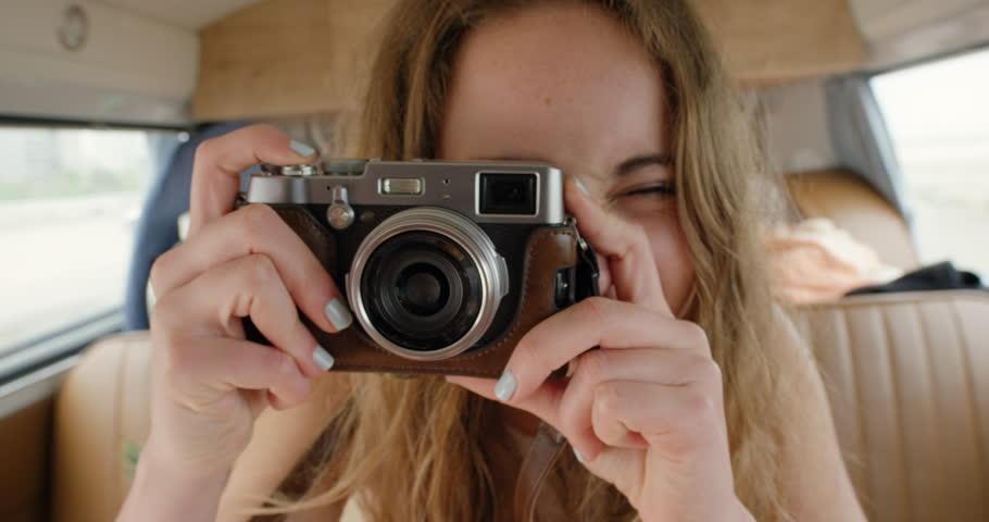 Portrait Teenage girl posing for camera taking photo wearing denim beach shorts smiling at festival in camper van on road trip adventure