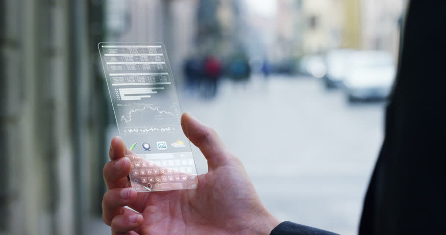 A businessman in the city,use the transparent phone with the latest technology to control finance and the markets of the financial bag. Concept:technology,business, immersive technology and future