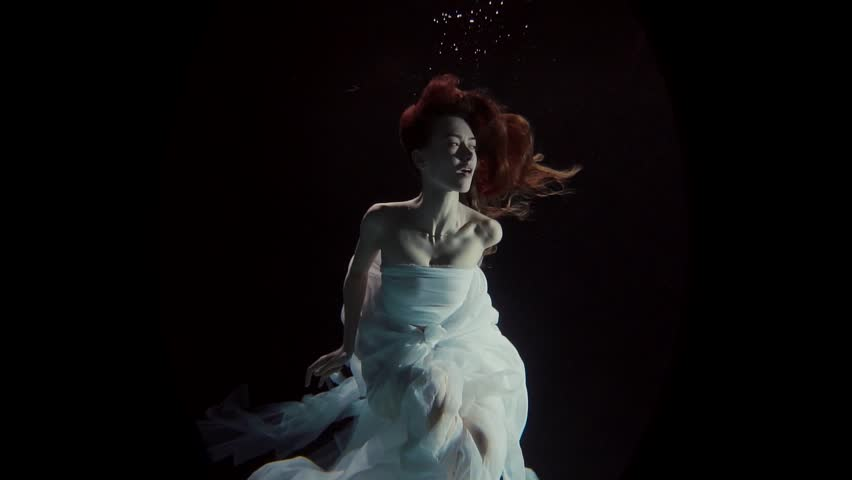 young woman swimming under the water on a black background