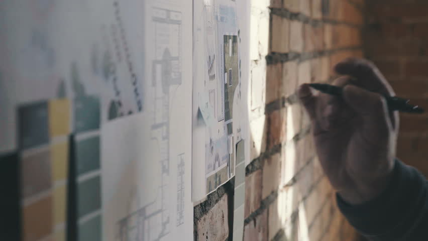 Stylish and modern cabinet in the loft style: A brick wall with notes and blueprints. Drawings and diagram of future buildings on the wall, there is blueprints and model house on the wall | Shutterstock HD Video #25055753