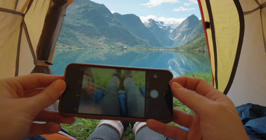 Camping woman lying in tent taking photo of feet with smart phone Close up of Girl wearing hiking boots relaxing on vacation POV Norway | Shutterstock HD Video #25065449