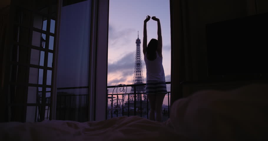 Young tourist woman stretching at sunrise on hotel terrace with view of Eiffel Tower Paris arms raised enjoying european travel adventure celebrating beautiful city   Shutterstock HD Video #25126154