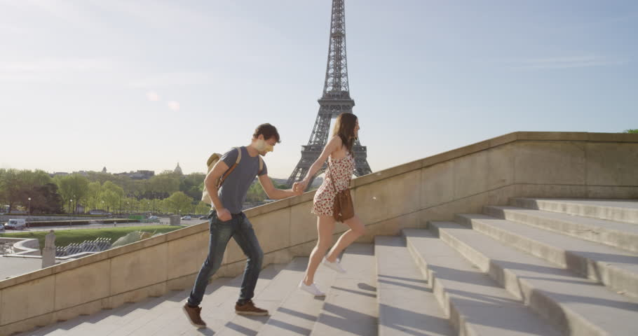 Young couple holding hands woman leading boyfriend walking towards view of Eiffel Tower Paris travel concept   Shutterstock HD Video #25130543