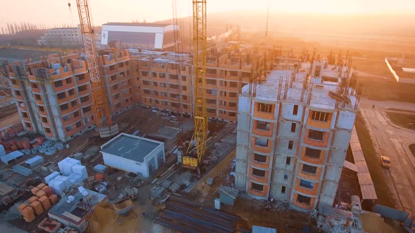 Construction site with a bird's eye on the Sunset. Video shooting with drone. Tower crane, excavator and sand. Flying over the construction site. The construction of the plant in the city. | Shutterstock HD Video #25137659