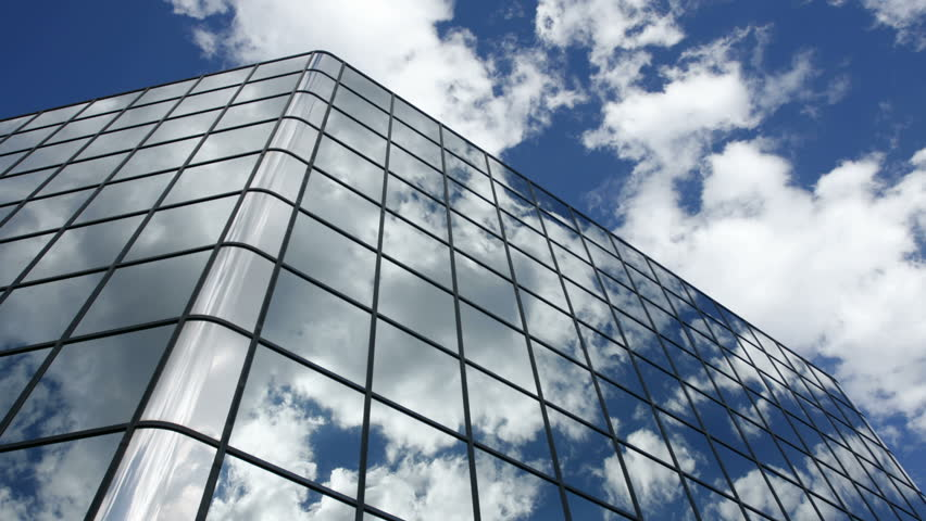 Timelapse of clouds reflected in the many mirrored facets of a modern office