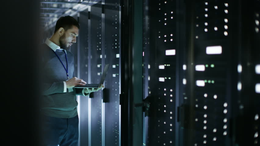 Male IT Technician Working on a Laptop Standing Before Open Server Rack Cabinet in Big Dara Center. Shot on RED EPIC-W 8K Helium Cinema Camera. | Shutterstock Video #25243019