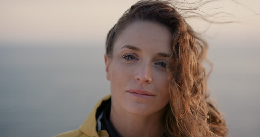Close up portrait of Young Woman smiling with Red hair blowing in wind looking at sunset over ocean Girl wearing yellow raincoat trekking in Scotland Slow Motion | Shutterstock HD Video #25252820