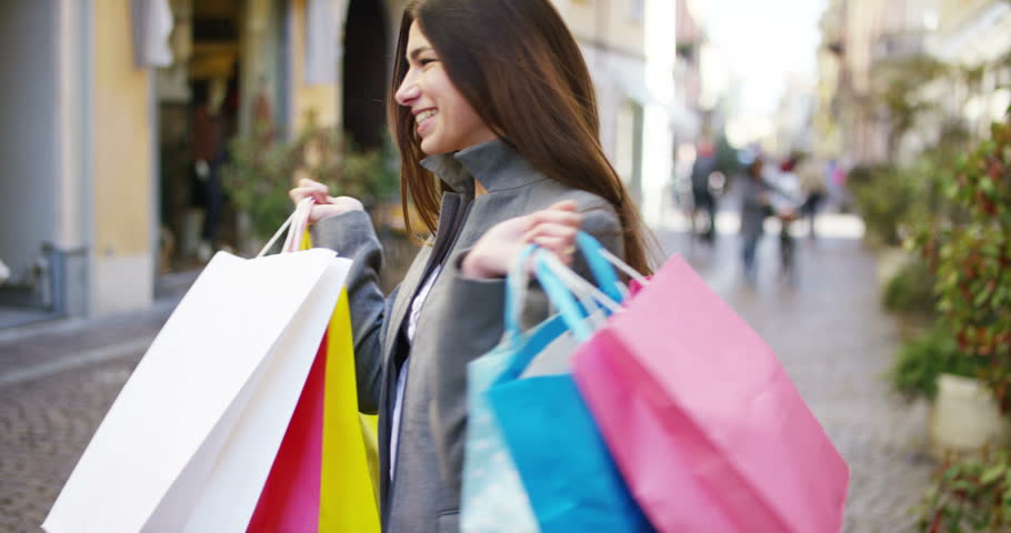 A beautiful woman walks through the city on shopping, she is very happy of purchases in the period sales. Concept: fashion, shopping, happiness and fashion bloggers | Shutterstock HD Video #25300157
