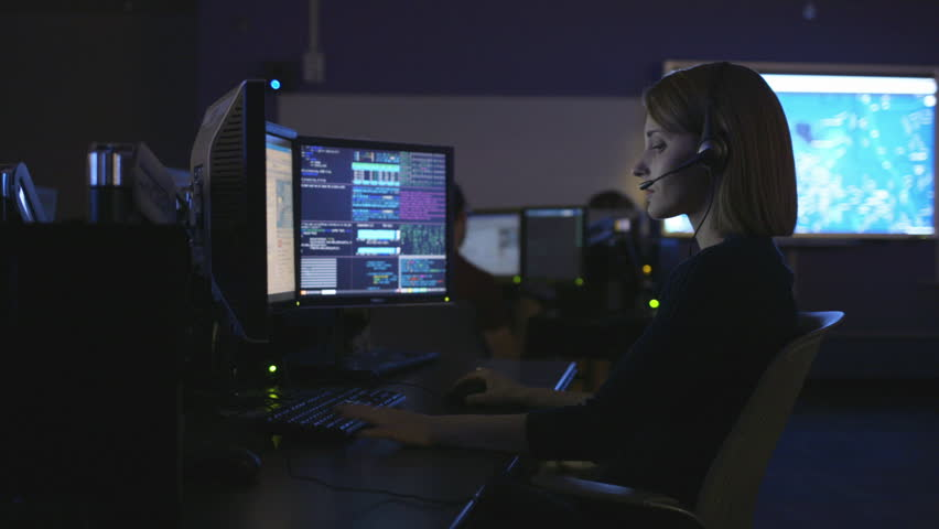 Woman on headset at desk in room with data on screens