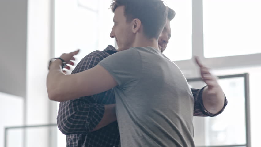 Medium shot of happy male friends meeting and pound hugging each other, then chatting about life