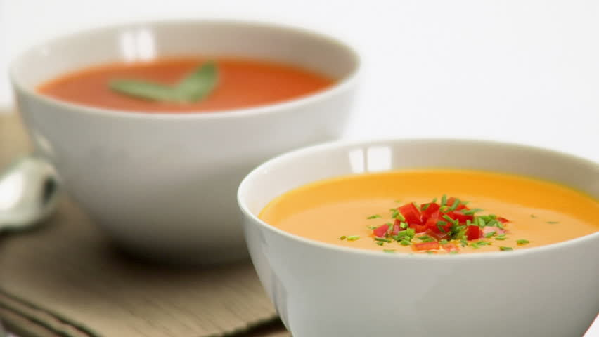 Two bowls of soup, with one red and the other yellow