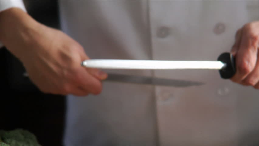 Chef sharpens knife with steel