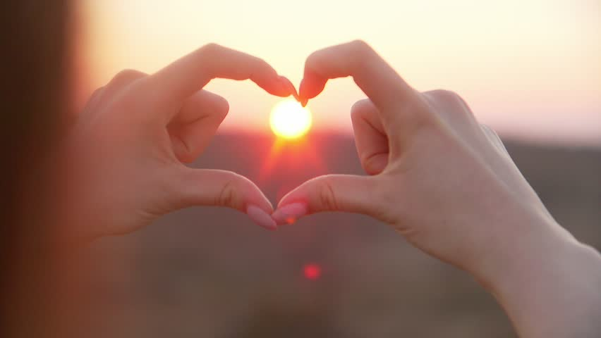 Female shapes heart with hands over the evening sun | Shutterstock HD Video #25521851