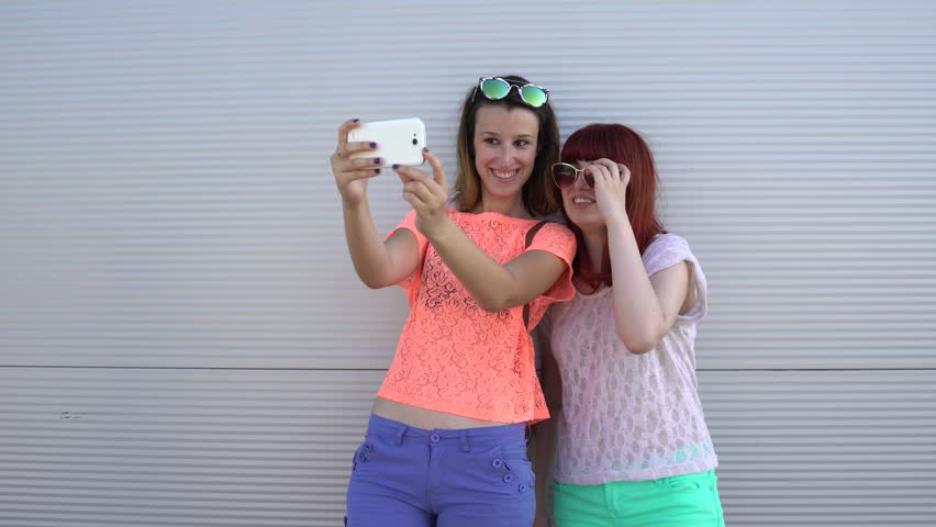 Two best friends girls having fun and making selfie. Two hipster girls taking selfie photos with smart phone.   Shutterstock HD Video #25567277