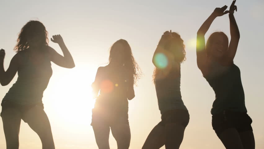 Four slim women dancing over sun on the beach