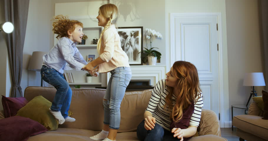 Little boy and girl jumping holding hands on the couch. Little boy and girl with their mother spending time together. Mother with kids having fun on sofa in the living room. Sister and brother. Happy